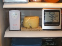 Honeywell brand model TM005X digital Hygrometer - Thermometer with wireless remote sensor, different readings due to different response speed from opening fridge door to take picture. Note poor mat material selection and surface stress cracks on 1 lb cheese after rapid surface dehydration in very low humdity kitchen fridge - CheeseForum.org